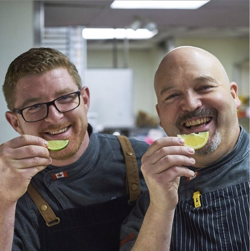 Two smiling Boston's employees holding lime slices like smiles.